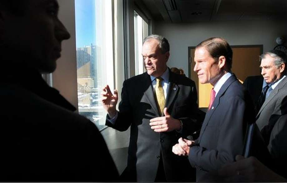 Carter Winstanley of Winstanley Enterprises, LLC, left, New Haven Mayor John DeStefano, U.S. Senator Richard Blumenthal, and  Bruce D. Alexander,Vice President for New Haven and State Affairs and Campus Development,  left to right, view the New Haven medical district from an upper level floor of 300 George Street during a briefing and discussion for Blumenthal on the Downtown Crossing project in the Route 34 Corridor on 1/13/11. The project will turn 11 acres of land downtown into developable and taxable land, reconnect neighborhoods and create opportunities for the expansion of New Haven's biotech industry.Photo by Peter Hvizdak / New Haven Register January 13, 2011       ph2237              #2332     Connecticut