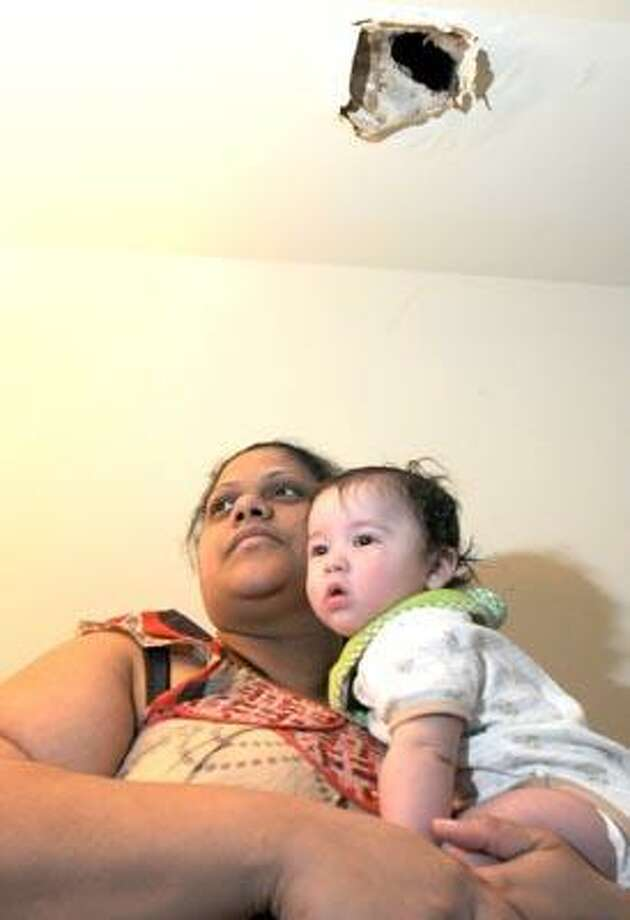 New Haven--Bryseida Hernandez holds her grandson Christian Quintero, 4 months, below the hole caused by a water leak in her ceiling.  The housing authority has failed to repair it after almost 12 months.  Photo by Brad Horrigan/New Haven Register-01.07.10.