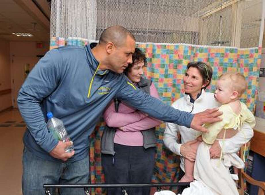 New Haven-- Former NFL star, (Kansas City Chiefs), Art Still, chats with 19-month-old Max Seufert-Youngling and his parents Renee Seufert, left, and Ann Youngling at Yale New Haven Children's Hospital. Max had just come out of surgery and was in the recovery room. They are from Milford. The Walter Camp All-Stars were visiting the children at the hospital, an annual event. Photo by Peter Casolino/New Haven Register01/14/11 Cas110114