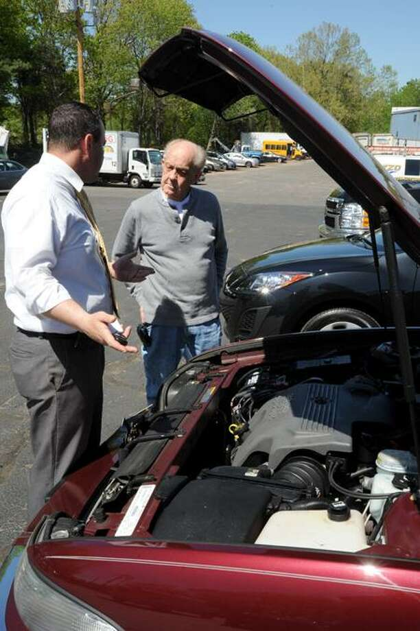 Rafael Mercado, left, sales consultant for Lee Partyka Chevrolet on Skiff Street in Hamden, goes over the basics of the new Buick Park Avenue Eddy Estep purchased from Lee Partyka. (VM Williams/Register)