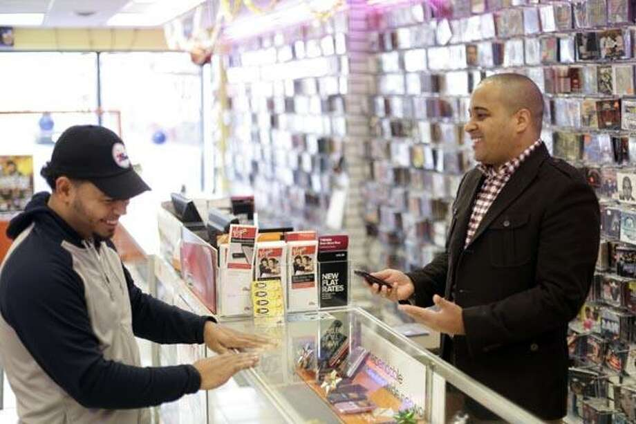 In this Dec. 22, 2010 photo, Ritmo Records owner Miguel Amador meets with customer Ramon Corona in one of his two stores in Camden, N.J. Five years ago, the majority of his revenue came from music CDs. Now his mobile device sales are up 50 percent from last year. (AP Photo/Matt Rourke) Photo: AP / Copyright 2011 The Associated Press. All rights reserved. This material may not be published, broadcast, rewritten or redistribu