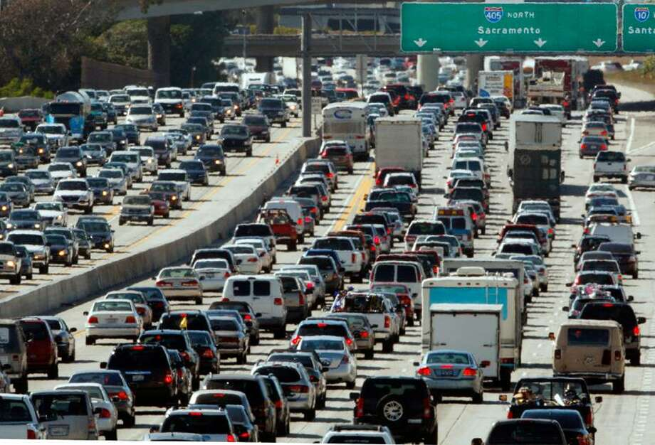 In this May 28, 2010 file photo, the rush hour commute starts in early afternoon and with greater intensity as traffic is jammed in both directions on Interstate 405 on the Westside of Los Angeles as commuters and vacationers hit the road.  Cheaper gas won't be enough to spur many more road trips this summer. Americans are too worried about their jobs and the economy to feel relief.  Economists and tourism experts are expecting only a small uptick in summer travelers. Gas prices are lower, but still high enough to keep lower-income Americans off the road. The job market is improving, but still shaky. And household debt remains high. The bulk of road trippers, experts say, are taking shorter trips, reducing food and entertainment expenses or staying closer to home to conserve cash.  Associated Press Photo: AP / AP2010