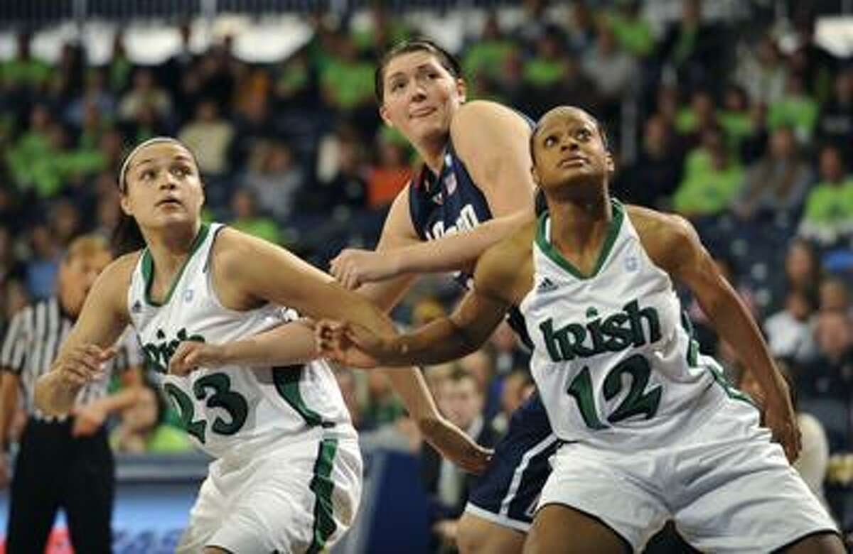 Connecticut center Stefanie Dolson battles for a rebound between Notre Dame guards Kayla McBride, left and Fraderica Miller, right, during first half action in an NCAA college basketball game Saturday, Jan. 8, 2011 in South Bend, Ind. (AP Photo/Joe Raymond)
