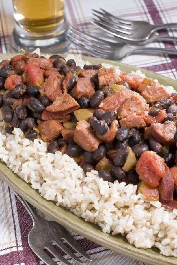 This Nov. 28, 2010 photo shows black bean and spicy sausage stew over brown rice in Concord, N.H. A simmering pot of stew is just right for a cold winter night and this recipe will heat you up without taking too much time in the kitchen. (AP Photo/Larry Crowe) Photo: AP / FR41490 AP