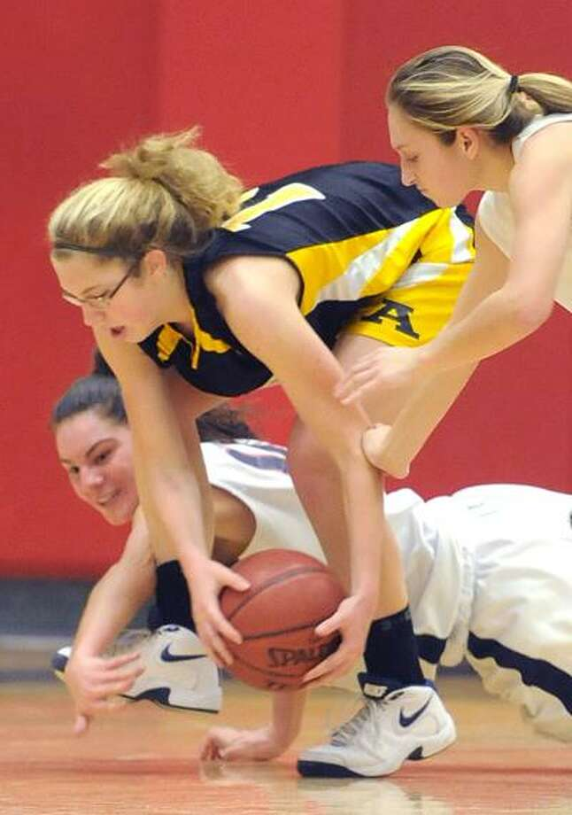 Milford--Amity's Tabitha Brown, center, grabs the ball between Foran players Cristina LaPenna, left, and Kelly Quinn, right, during Tuesday night's game in Milford.  Brad Horrigan/New Haven Register-01.11.11.