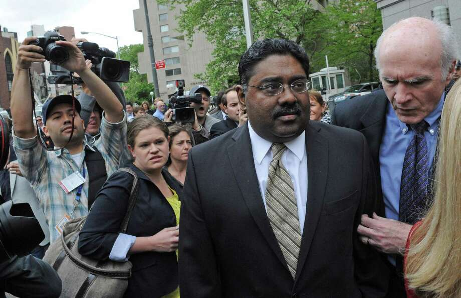 Billionaire co-founder of Galleon Group Raj Rajaratnam exits Manhattan federal court with his attorney terence Lynam Wednesday in New York. The former Wall Street titan was convicted of making a fortune by coaxing a crew of corporate tipsters to give him an illegal edge on blockbuster trades in technology and other stocks.(AP Photo/ Louis Lanzano) Photo: ASSOCIATED PRESS / AP2011