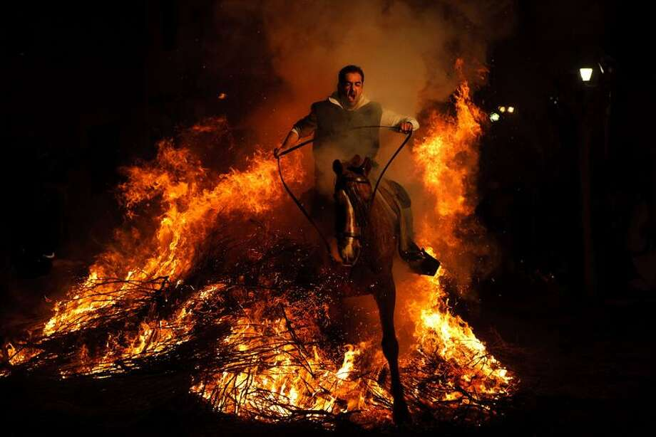 """A man rides a horse through a bonfire in San Bartolome de Pinares, Spain, Monday, in honor of Saint Anthony, the patron saint of animals. On the eve of Saint Anthony's Day, hundreds ride their horses trough the narrow cobblestone streets of the small village of San Bartolome during the """"Luminarias,"""" a tradition that dates back 500 years and is meant to purify the animals with the smoke of the bonfires and protect them for the year to come. Associated Press Photo: ASSOCIATED PRESS / AP2011"""