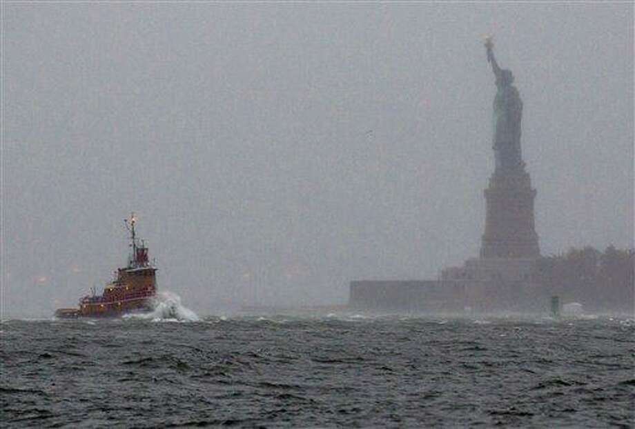 Waves crash over the bow of a tug boat as it passes near the Statue of Liberty in New York Mondayas rough water as the result of Hurricane Sandy churned the waters of New York Harbor. AP Photo/Craig Ruttle Photo: AP / FR61802 AP