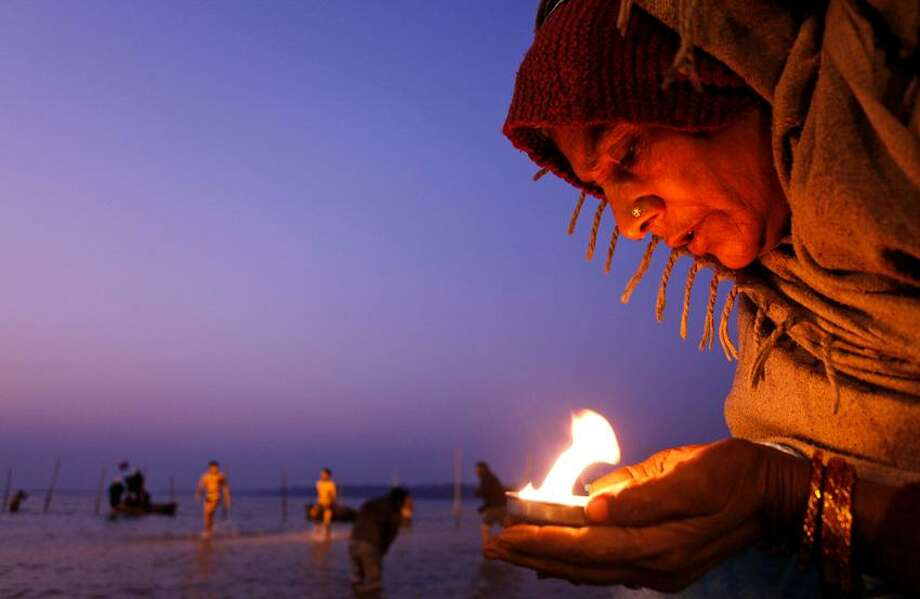 """Hindu devotee holds an oil lamp and offers prayers to the Sun god at the Sangam, the confluence of the rivers Ganges, Yamuna and the mythical Saraswati, on Makar Sankranti festival, that falls during the annual traditional fair of Magh Mela, in Allahabad, India, Saturday. Hundreds of thousands of devout Hindus take a bath at the confluence during the astronomically auspicious period of over 45 days celebrated as """"Magh Mela"""" to rid themselves of their sins and attain prosperity. Associated Press Photo: ASSOCIATED PRESS / AP2012"""