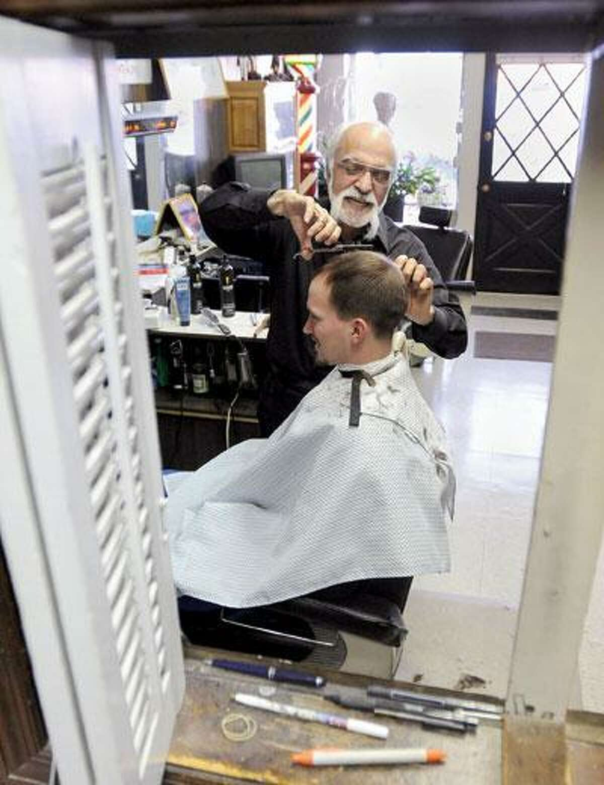 Anthony Gamberdella has been cutting hair in New Haven for 50 years. He's retiring in April. (Brad Horrigan/Register)