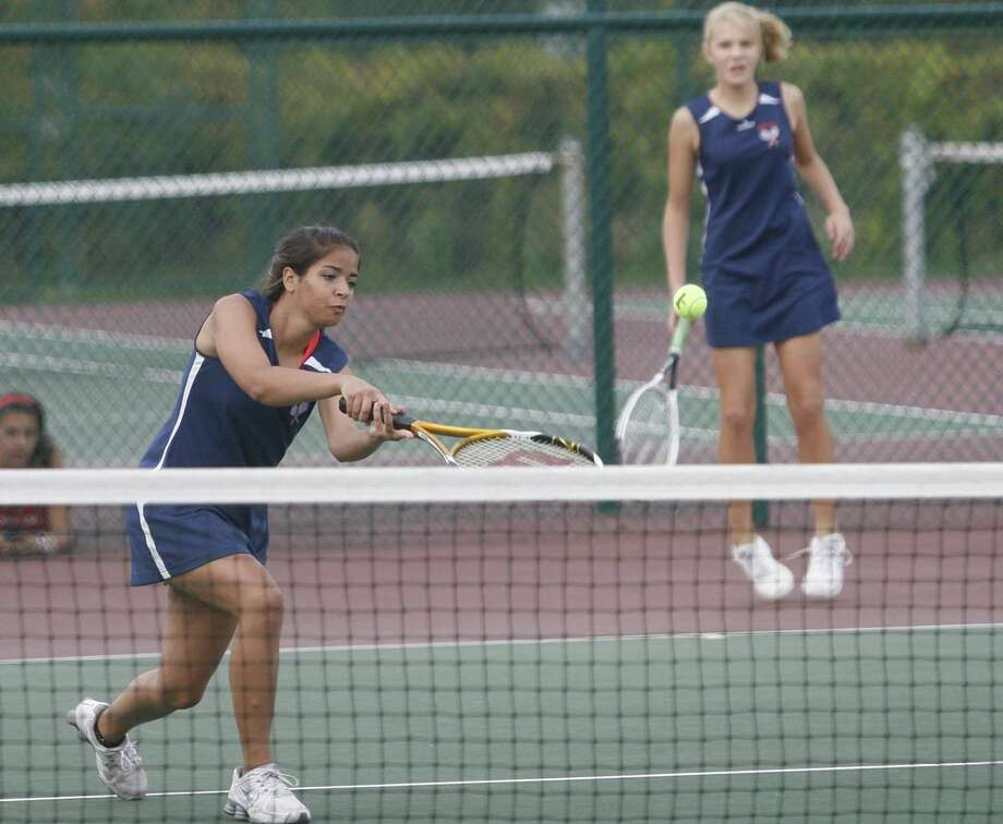 """Dispatch Staff Photo by JOHN HAEGER <a href=""""http://twitter.com/oneidaphoto"""">twitter.com/oneidaphoto</a>  Oneida's Destiny Pagan returns a shot to New Hartford's ? and ? As doubles partner Jillian Brodock looks on during a match in New Hartford on Tuesday, Oct. 11, 2011."""