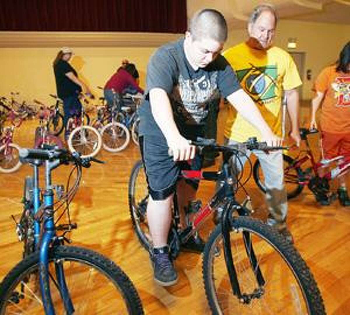 Photo by JOHN HAEGER Robin White of Hamilton helps Kenneth Thurston, 12, of Morrisville, find the right bike during the Community Bike Give Away on Sunday, May 8, 2011 in Oneida.