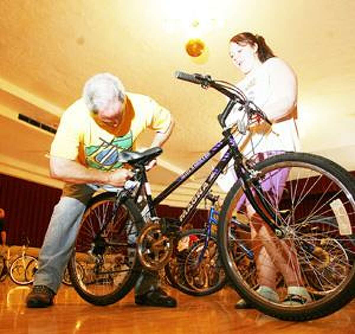 Photo by JOHN HAEGER Robin White of Hamilton adjusts the seat on a bike for Paige VanDusen,14, of Oneida, during the Community Bike Give Away on Sunday, May 8, 2011 in Oneida.