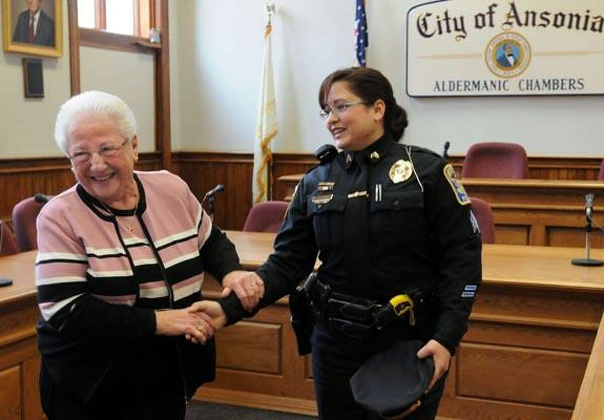 Newly sworn in Ansonia Police Sgt. Jennifer Pella is congratulated by Ansonia's first woman police commissioner Ann Pitney left at Ansonia City Hall. Pella is Ansonia's first woman police sergeant. With video. Photo by Mara Lavitt/New Haven Register1/4/11