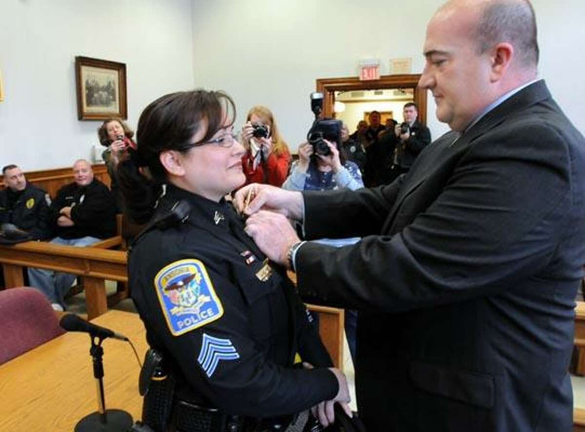 Newly sworn in Ansonia Police Sgt. Jennifer Pella gets her badge pinned on by her fiance Sgt. Randy Guisto at Ansonia City Hall. Pella is Ansonia's first woman police sergeant. With video. Photo by Mara Lavitt/New Haven Register1/4/11