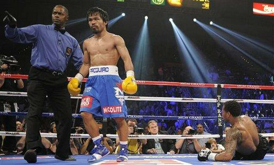 Manny Pacquiao, center is directed to his corner by referee Kenny Bayless, left, after knocking down Shane Mosley in the third round during a WBO welterweight title bout, Saturday, May 7, 2011, in Las Vegas.  (AP Photo/Mark Terrill) Photo: AP / AP