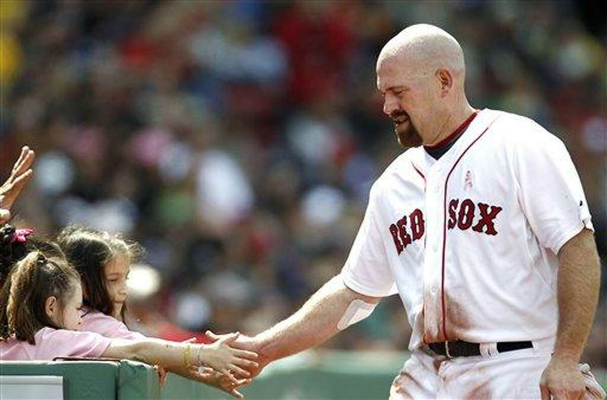 Boston Red Sox's Kevin Youkilis gets congratulations from two fans after scoring during the third inning of a baseball game against the Minnesota Twins at Fenway Park in Boston on Sunday, May 8, 2011. (AP Photo/Winslow Townson)
