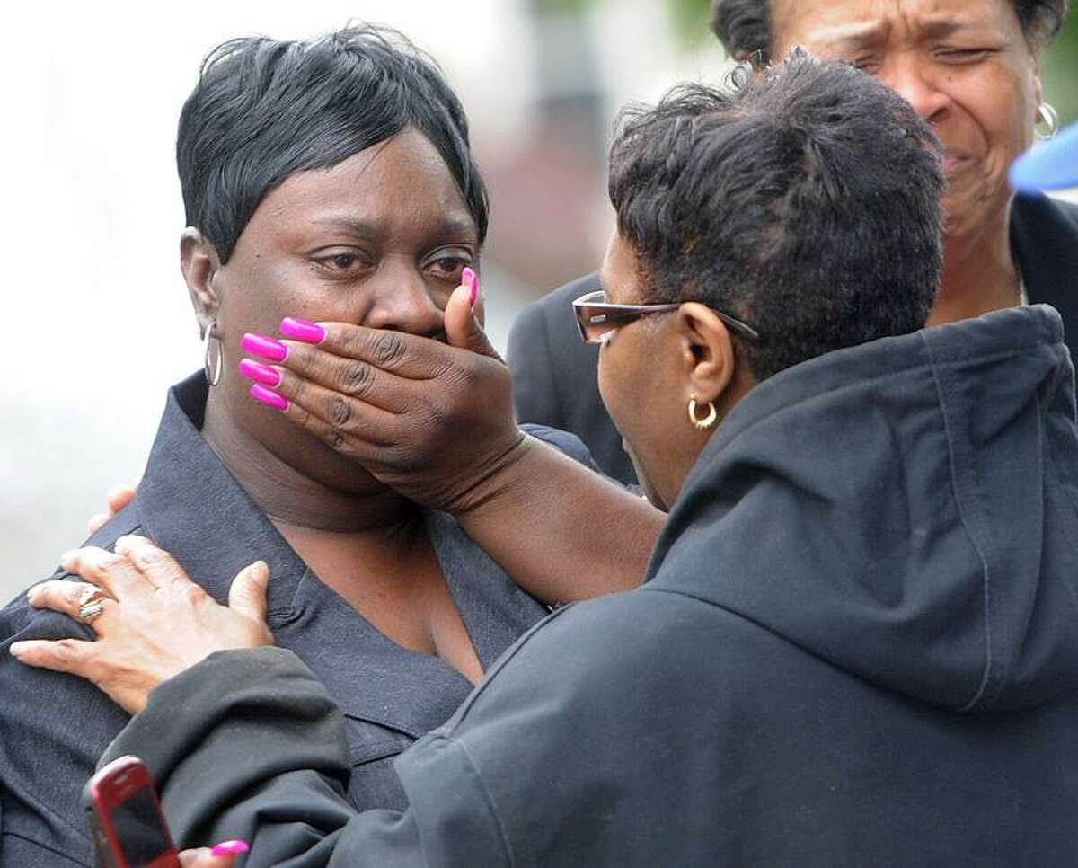 A tenant's family members react to the fire. Two of the floors were inhabited. Third-floor residents escaped after they were alerted to the blaze. People who lived on the first floor came home from church to find their apartment had burned. (Photo by Brad Horrigan/Register)