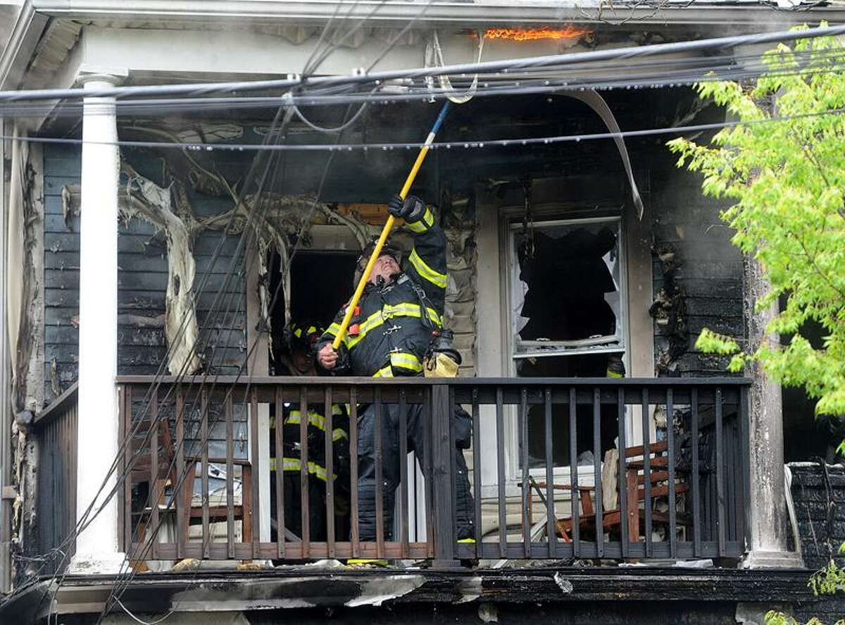 A New Haven firefighter battles flames creeping from the roof of 375 Sherman Parkway Sunday afternoon. No one was injured in the three-alarm blaze, which remains under investigation, police said. Neighbor Ella Moorer said she called 911 around 3:30 p.m. after she saw fire inside the first floor of the three-family building. (Photo by Brad Horrigan/Register)