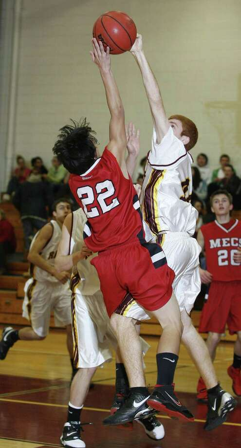Dispatch Staff Photo by JOHN HAEGER M-E's Dakota Miller (22) has his shot blocked by Canastota's Richard Mitchell (44) in the first half of the game at Canastota on Tuesday, Jan. 4, 2011.