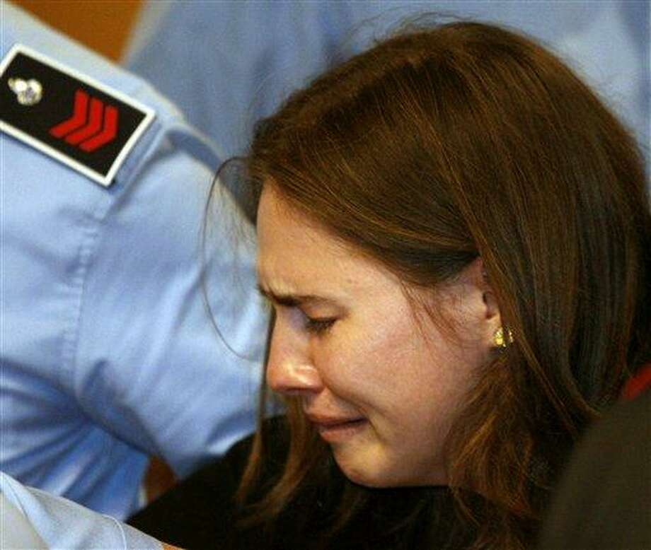 Amanda Knox breaks in tears as she is taken away after hearing the verdict that overturns her conviction and acquits her of murdering her British roommate Meredith Kercher, at the Perugia court, central Italy, Monday, Oct. 3, 2011. Italian appeals court threw out Amanda Knox's murder conviction Monday and ordered the young American freed after nearly four years in prison for the death of her British roommate. Knox collapsed in tears after the verdict overturning her 2009 conviction was read out. Her co-defendant, Italian Raffaele Sollecito, also was cleared of killing 21-year-old Meredith Kercher in 2007. (AP Photo/Pier Paolo Cito) Photo: AP / Copyright 2011 The Associated Press. All rights reserved. This material may not be published, broadcast, rewritten or redistributed.