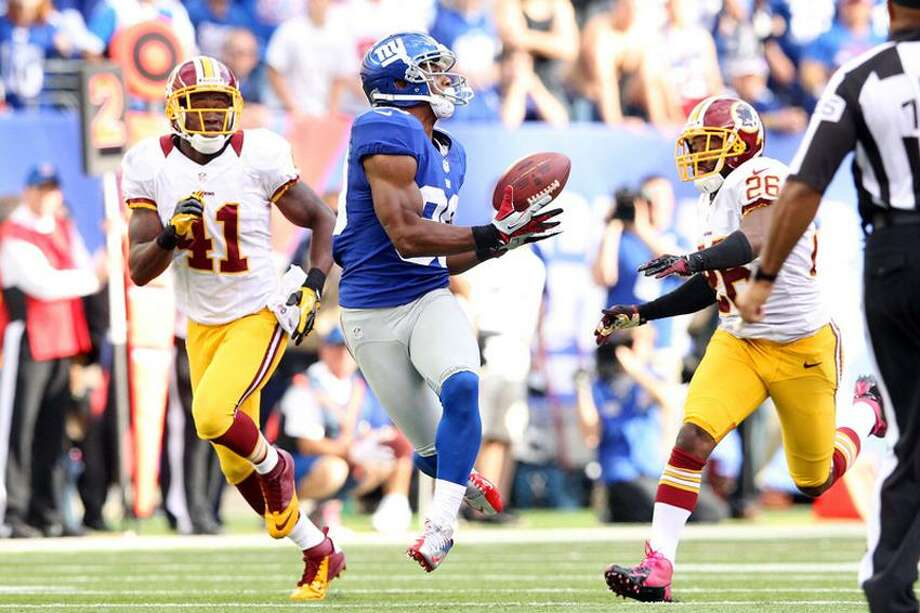 October 21, 2012; East Rutherford, NJ, USA; New York Giants wide receiver Victor Cruz (80) catches a game-winning touchdown pass against Washington Redskins safety Madieu Williams (41) and corner back Josh Wilson (26) during the fourth quarter of an NFL game at MetLife Stadium. Mandatory Credit: Brad Penner-US PRESSWIRE Photo: US PRESSWIRE / Brad Penner