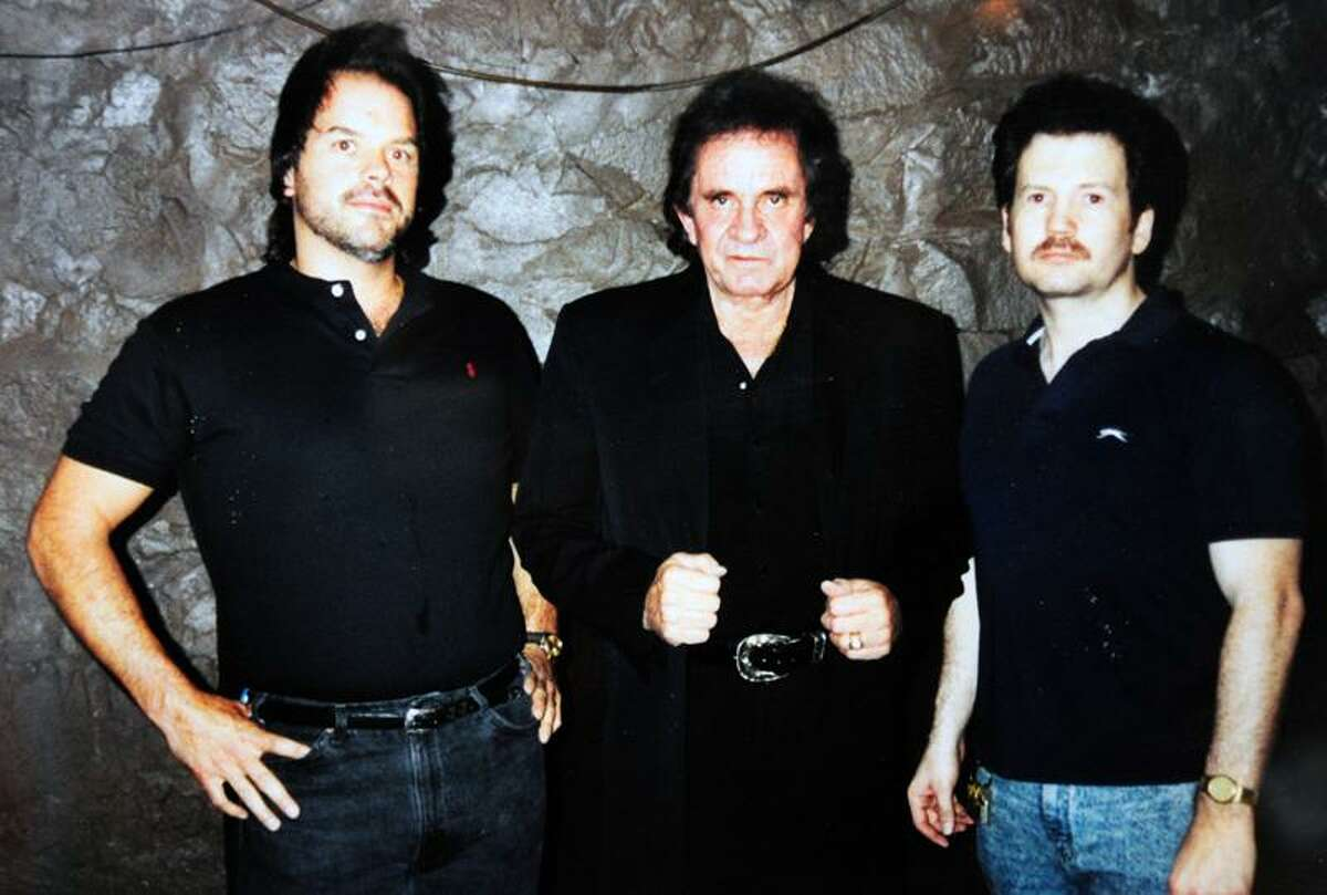 Mike Spoerndle, left, and Brian Phelps, right, are photographed with Johnny Cash at Toad's Place in New Haven.