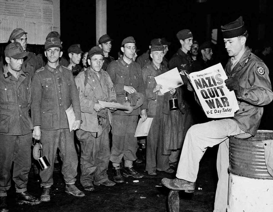 Pfc. Clarence K. Ayers of Evansville, Ind., reads the news of V-E Day as newly arrived German prisoners stand of a New York City pier, May 8, 1945. Associated Press Photo: ASSOCIATED PRESS / AP1945