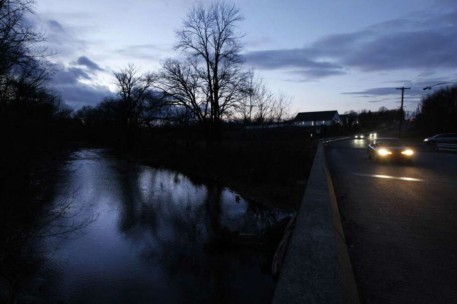 In this Dec. 15, 2010 photo, a car passes over the Neshaminy Creek after sunset  in Chalfont Pa. According to state records treated drilling wastewater was discharged through the town sewage plant into the Neshaminy Creek. The natural gas boom gripping parts of the U.S. has a nasty byproduct: wastewater so salty, and so polluted with metals like barium and strontium, most states require drillers to get rid of the stuff by injecting it down shafts thousands of feet deep. Not in Pennsylvania, one of the states at the center of the gas rush. There, the liquid that gushes from gas wells is only partially treated for substances that could be environmentally harmful, then dumped into rivers and streams from which communities get their drinking water.  (AP Photo/Matt Rourke) Photo: ASSOCIATED PRESS / AP2010