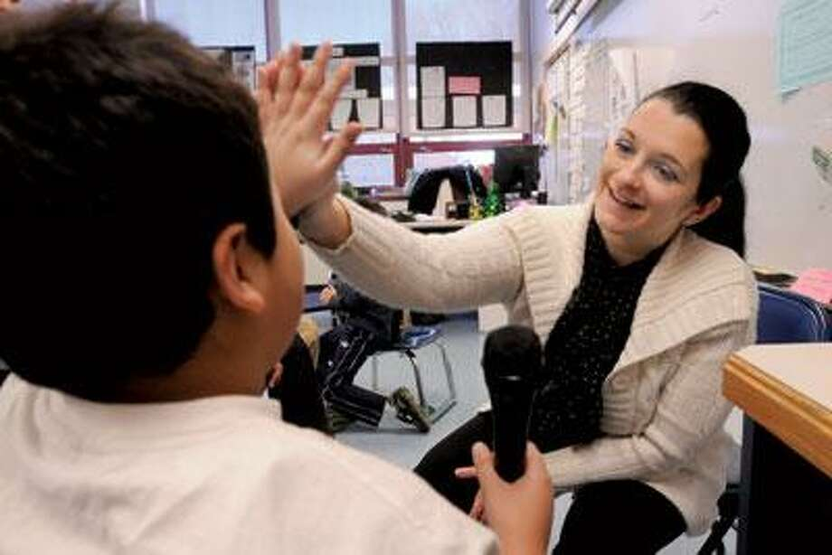 Blanka Jamsek, a teacher at New Haven's Katherine Brennan/ Clarence Rogers School, congratulates one of her special needs students for a good answer to her question. (Mara Lavitt/Register)
