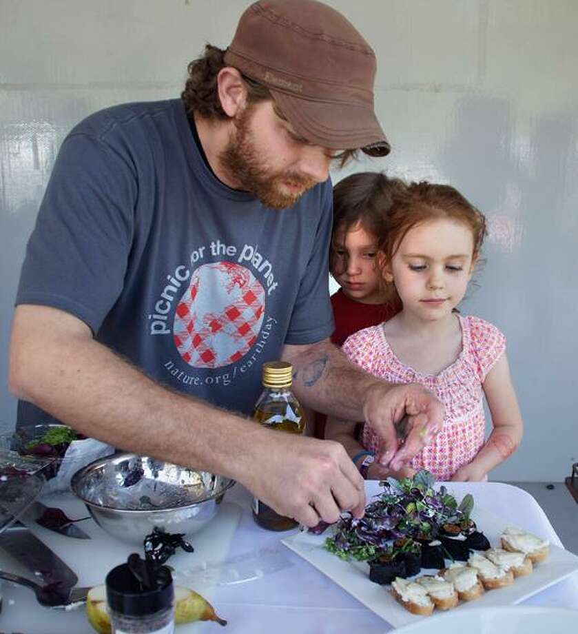Peter Casolino/Register photo: Jason Sobocinski, owner of Caseus Fromagerie Bistro, works with two helpers from the audience, Shayna Bailis, 4, of Hamden, center, and Beyla Ridky, 5, of New Haven during the Picnic Battle For the Planet chef competition at East Rock Park.
