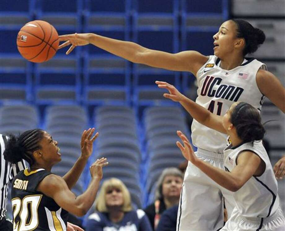 Connecticut's Kiah Stokes, top right, blocks a shot by Towson's Markell Smith, left, as Connecticut's Bria Hartley, bottom right, defends in the first half of an NCAA college basketball game in Hartford, Conn., Wednesday, Nov. 30, 2011. (AP Photo/Jessica Hill) Photo: AP / AP2011