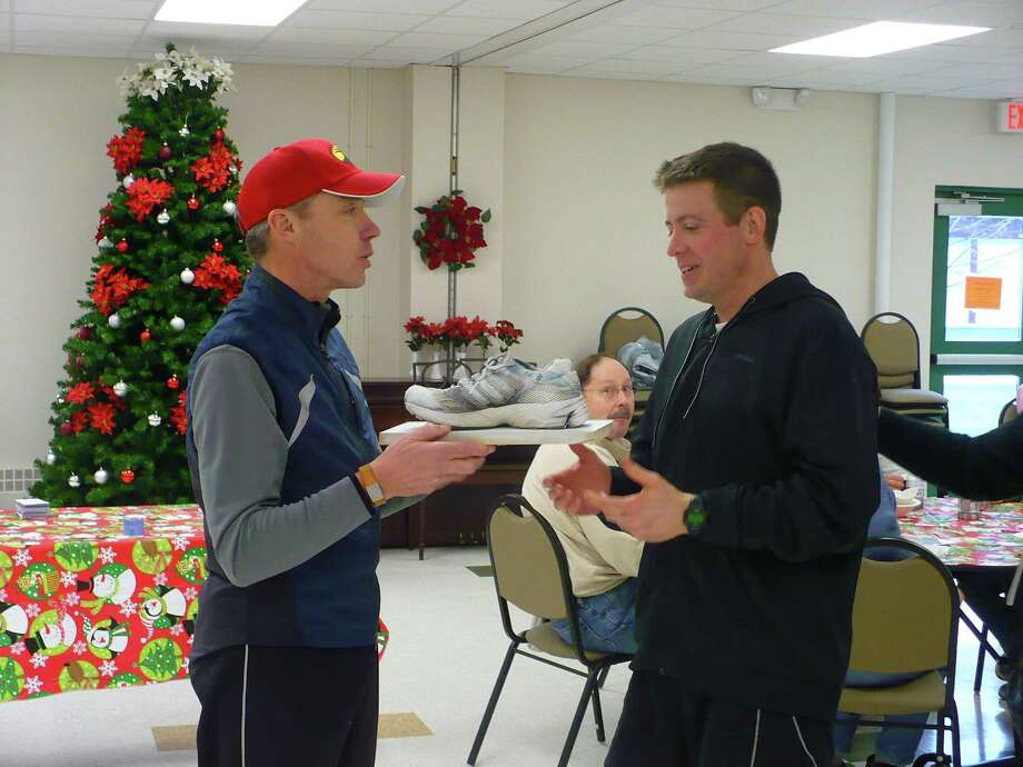 Dispatch Staff Photo by DAVID M. JOHNSON Chris Deyo, right, accepts the Frozen Foot award from Dan DeFrees at the 2011 New Year's Resolution Fun Run and Walk Saturday, Jan. 1, 2011 at the Veterans Memorial Parks & Rec building in Chittenango. Katie Bombard won the women's award.