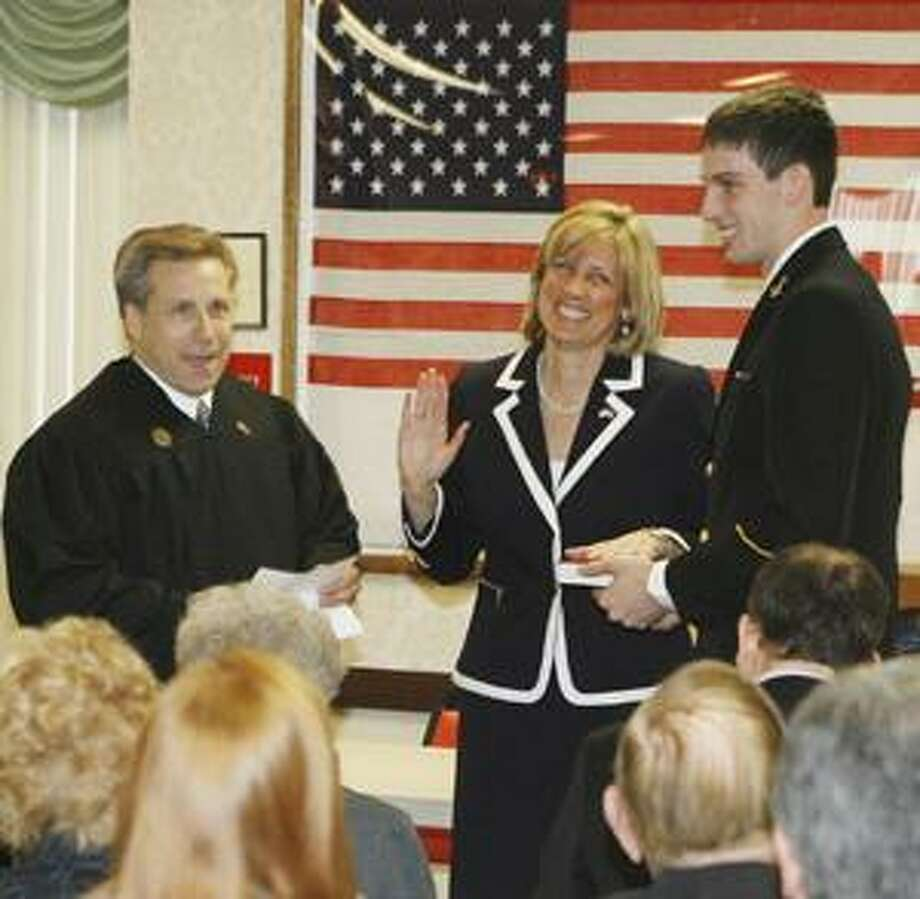Photo by JOHN HAEGER Honorable John Brennan, right, administers the oath of office to Claudia Tenney for the 115th Assembly District as her son, Trey Cleary, holds the Bible on Saturday, Jan. 1, 2011 in New Hartford.