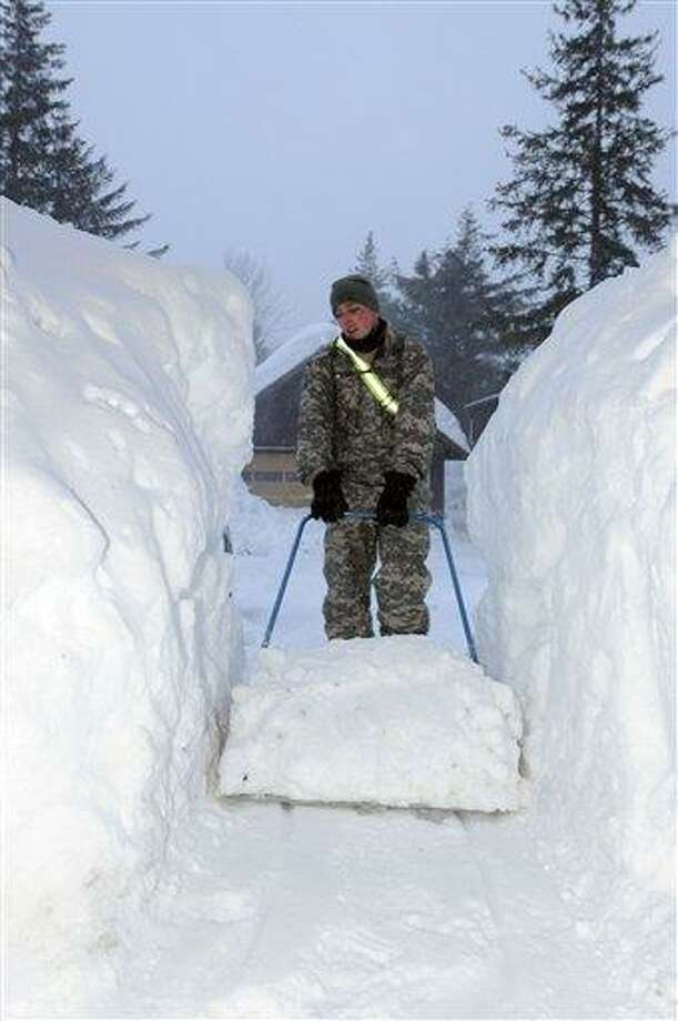 In this photo provided by the Alaska National Guard, a Guardsman clears a walkway of snow earlier this week in Cordova, Alaska. There are currently 57 National Guardsmen assisting citizens in this small Alaska town. Associated Press Photo: AP / Alaska National Guard