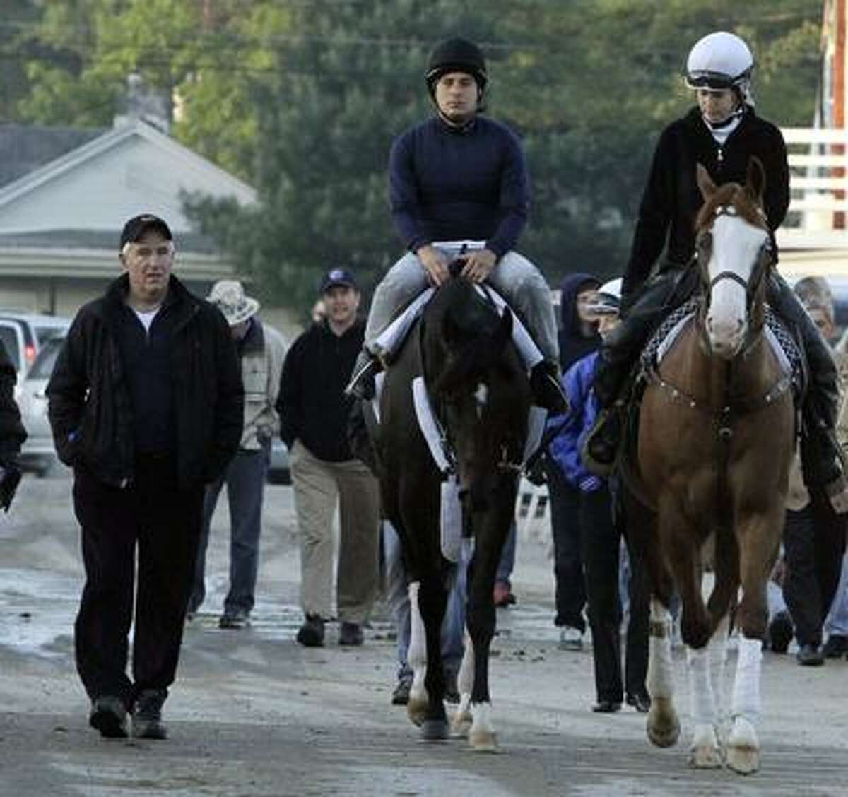 Trainer Nick Zito, left, walks with Exercise rider Carlos Correa as they take Kentucky Derby entrant Dialed In for a workout at Churchill Downs Thursday, May 5, 2011, in Louisville, Ky. At right is assistant trainer Stacy Prior. (AP Photo/Garry Jones)