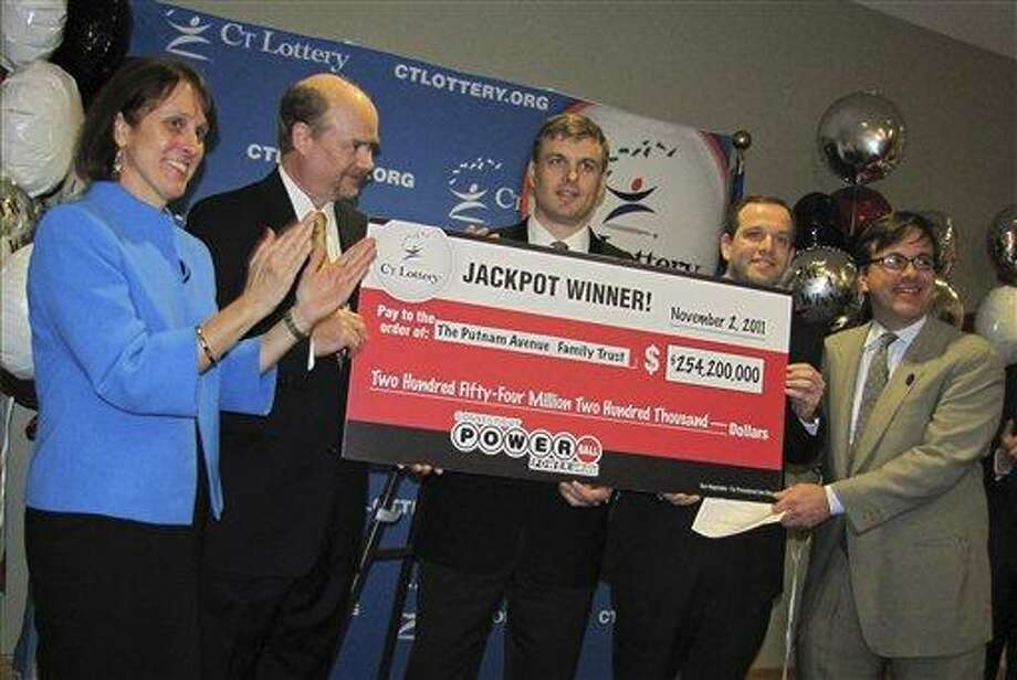 In this photo provided by the Connecticut Lottery in Greenwich, Conn., wealth managers Tim Davidson, second left, Greg Skidmore, center, and Brandon Lacoff, second right, pose Monday, Nov. 28. 2011 with a ceremonial check after the men claimed a $254.2 million Powerball jackpot won on Nov. 2, in Rocky Hill, Conn. The jackpot was the largest ever won in Connecticut and the 12th biggest in Powerball history. The largest previous lottery jackpot in Connecticut was $59.5 million in June 2005. (AP Photo/Connecticut Lottery) Photo: AP / Connecticut Lottery