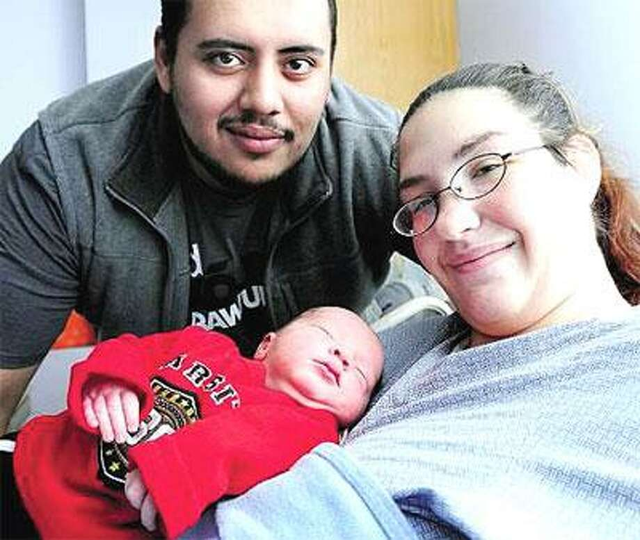 Emanuel Velez, top, and Heather Lafogg show off their newborn son, Angel Velez, who was born at 2:03 a.m. Saturday at the Hospital of Saint Raphael in New Haven. (Arnold Gold/Register)