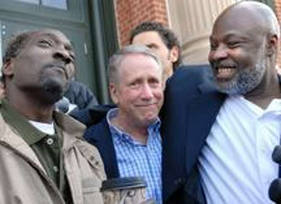 "Ronald Taylor, left, and George Gould, right, with Private Investigator G.J. ""Jerry"" O'Donnell of Chesire,  center,  celebrating their release in front of Rockville Superior Court Thursday after spending 16-years in prison for a 1993 murder in Fair Haven that they did not commit. O'Donnell was instrumental in gathering the evidence of their innocence.  PETER HVIZDAK/Register"