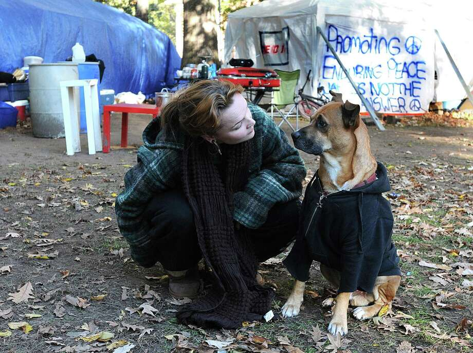 In this file photo from November, Occupy New Haven protester Katherine Ziebell of Milford, plays with her dog Barley during a quiet Friday afternoon among the tents. Peter Casolino/New Haven Register   11/04/11