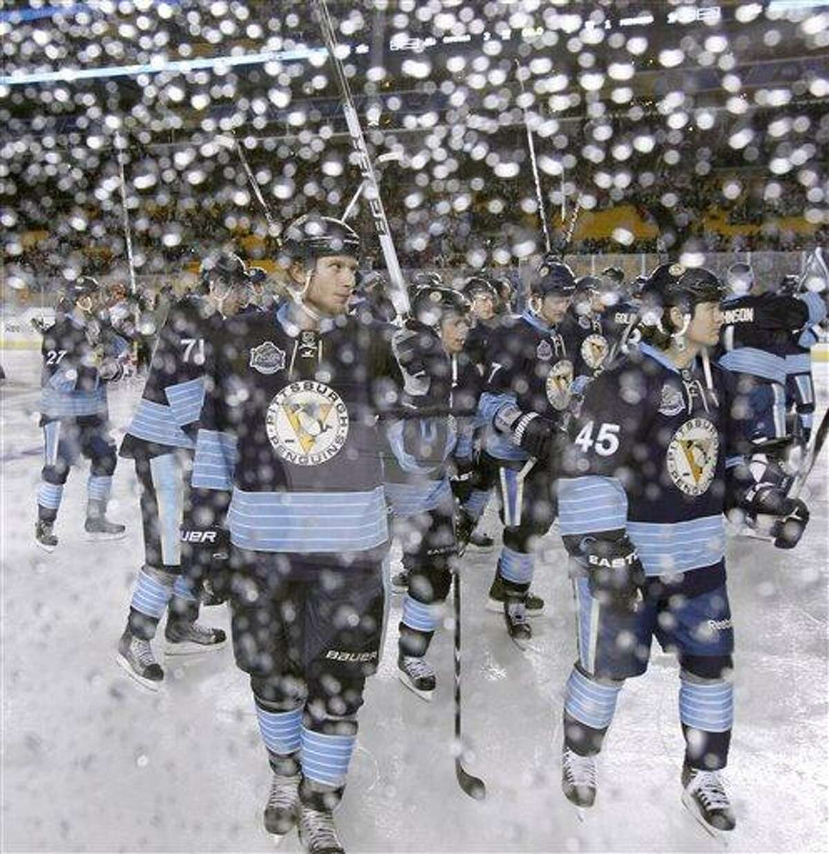 Pittsburgh Penguins' Jordan Staal, center, is seen through the raindrop covered glass bordering the rink as he and the team raise their sticks in tribute to the fans after the third period of the NHL Winter Classic outdoor hockey game in Pittsburgh on Saturday, Jan. 1, 2011. The Washington Capitals won 3-1. (AP Photo/Keith Srakocic)