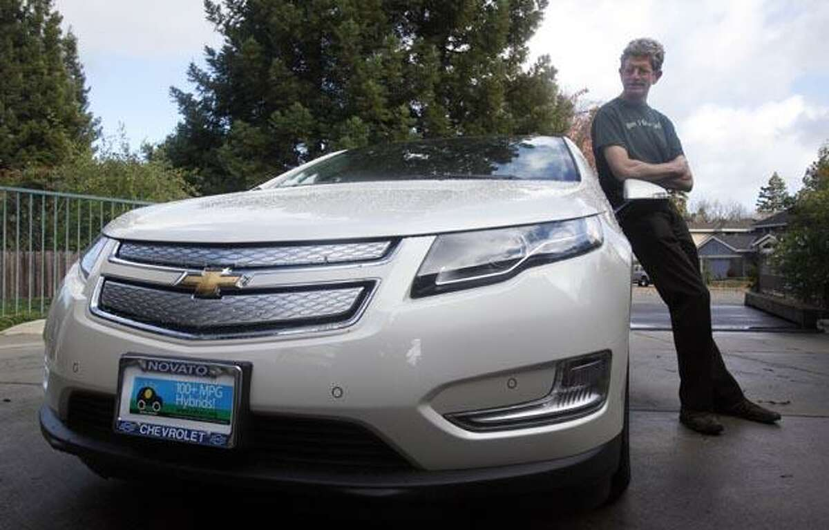 Felix Kramer, founder of CalCars, poses for a photograph next to his new Chevy Volt electric car in Redwood City, Calif., Wednesday, Dec. 29, 2010. In December, dozens of car buyers exhibited strange behaviors: They accepted the keys in front of a crowd of people, many snapping photos and taking video of the moment they picked up their new electric cars, marking the first sales of mass-produced battery-powered cars in the U.S. (AP Photo/Jeff Chiu)