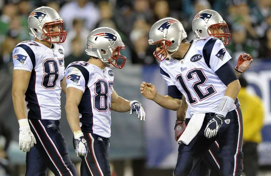 New England Patriots quarterback Tom Brady, right, reacts with wide receiver Wes Welker, second from left, and tight end Rob Gronkowski (87), left, after Welker's touchdown during the first half of an NFL football game against the Philadelphia Eagles, Sunday, Nov. 27, 2011, in Philadelphia. (AP Photo/Michael Perez) Photo: AP / AP2011