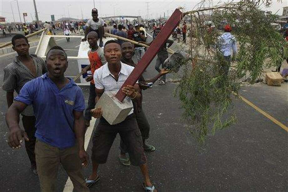 "Angry youths protest on a Lekki road on the third day of a nationwide strike following the removal of a fuel subsidy by the government in Lagos, Nigeria, Wednesday. Nigeria's government is warning that a paralyzing national strike risks ""anarchy"" in the oil-rich nation, as demonstrations over spiraling fuel prices and government corruption entered their third day Wednesday. Associated Press Photo: AP / AP"