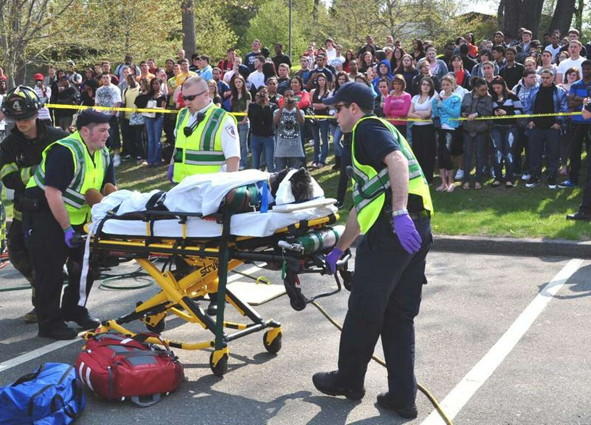 Ansonia police and firefighters take part in a mock crash to illustrate the tragedy of drunken and careless driving.