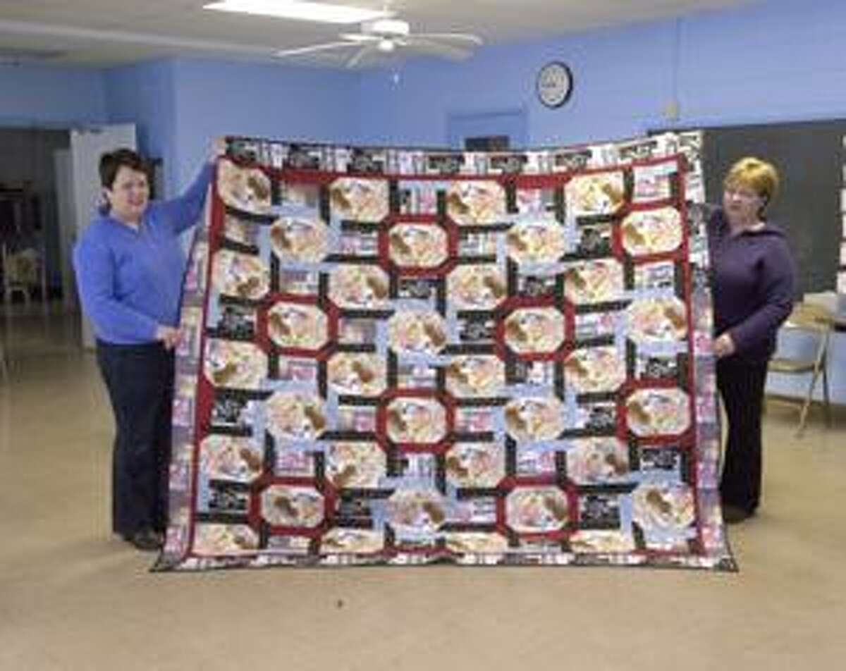 """SUBMITTED PHOTO Jeannine Masucci and Karen Puglisi of Canastota hold the """"Labor of Love"""" quilt Masucci won at the annual Labor of Love festival in Canastota."""