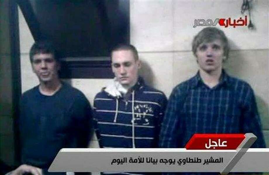 FILE - In this Tuesday, Nov. 22, 2011 file image from Egyptian state television, three American students are displayed to the camera by Egyptian authorities following their arrest during protests in Cairo, where an Egyptian official said they were throwing firebombs at security forces. A spokeswoman for the American University in Cairo identified the students as Luke Gates, a 21-year-old Indiana University student from Bloomington, Ind.; Derrik Sweeney, a 19-year-old Georgetown University student from Jefferson City, Mo.; and Gregory Porter, a 19 year-old Drexel University student from Glenside, Pa. An official says an Egyptian court has ordered release of 3 US students arrested during Cairo unrest.(AP Photo/ Egyptian TV, File) Photo: AP / EGYPTIAN TV
