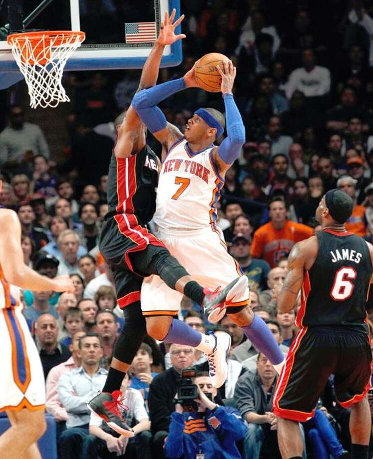 New York Knicks' Carmelo Anthony (C) shoots over Miami Heat's Dwyane Wade (L) as Heat's LeBron James looks on (R) in the second quarter of the Knicks' win in Game 4 of their NBA Eastern Conference basketball playoff series in New York, May 6, 2012.  REUTERS/Mike Segar (UNITED STATES - Tags: SPORT BASKETBALL) Photo: REUTERS / X90033