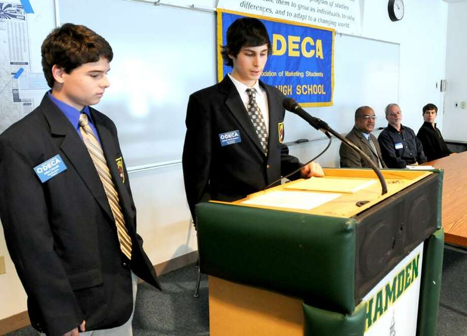John Cifarelli and Jarrett Neckameyer, both members of the Hamden High School Distributive Education Clubs of America, introduce entrepreneurs visiting the club recently at the school. Peter Hvizdak/Register