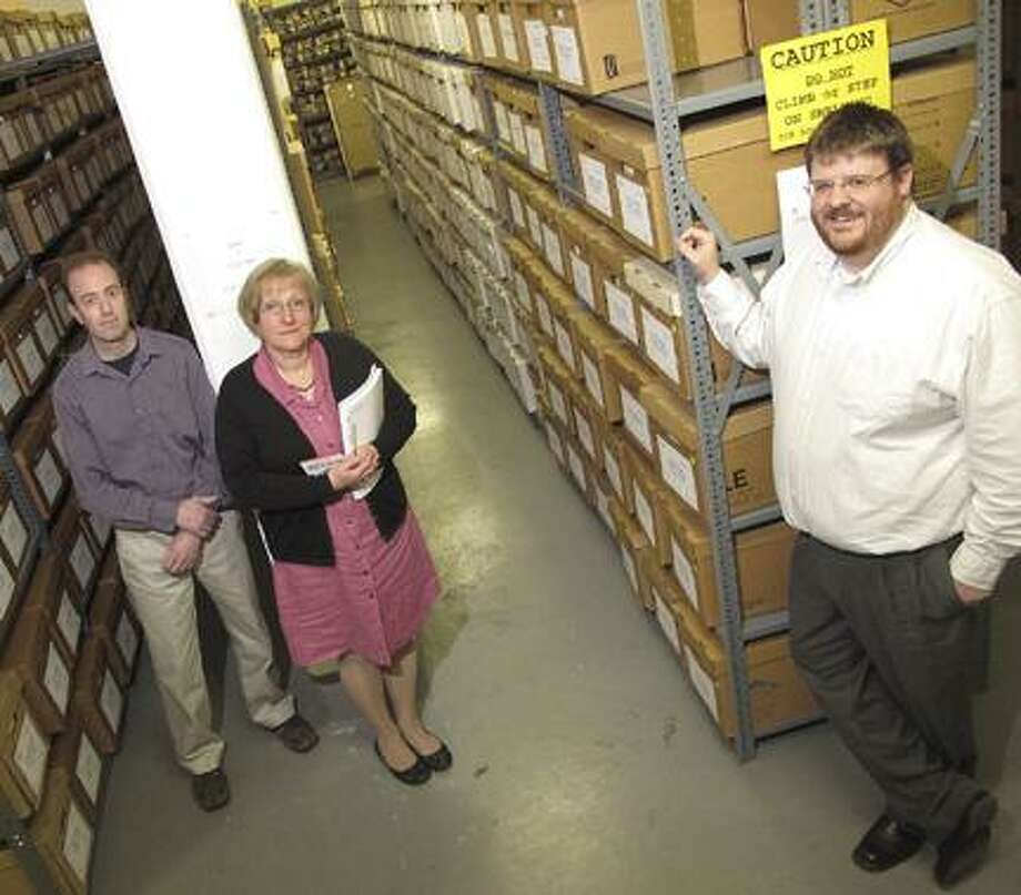 Photo by JOHN HAEGERRecords management coordindator Kevin Orr,  deputy county clerk Denise Roe and Madison County historian Matt Urtz with some of the 20 tons of documents of Madison County.